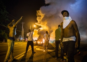 Demonstrators stand in the middle of West Florissant as they react to tear gas fired by police during ongoing protests in reaction to the shooting of Brown, in Ferguson